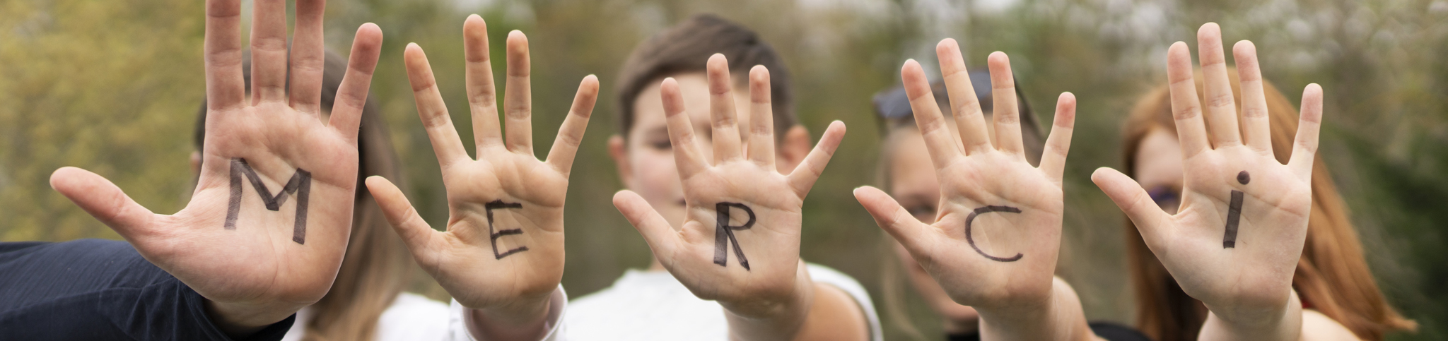 mains ou s'ont inscrites les lettres du mot merci